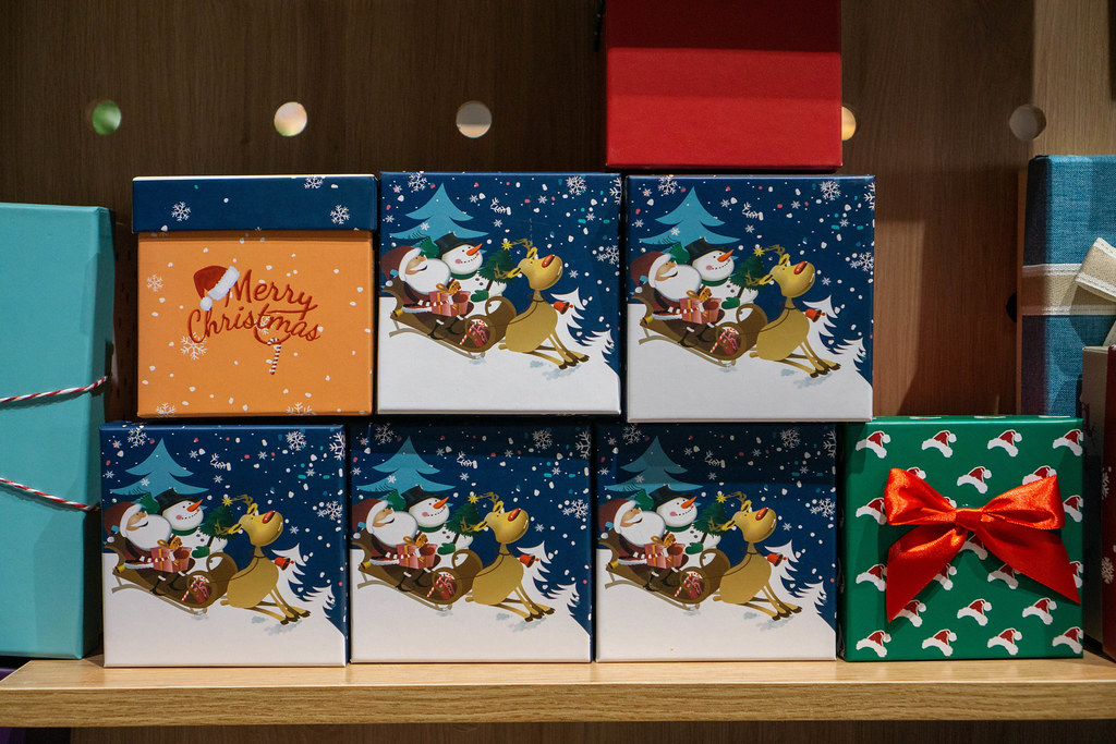 Small Paper Present Box in Christmas Design with Santa Claus, Snowman and Raindeer displayed in a Store Shelf
