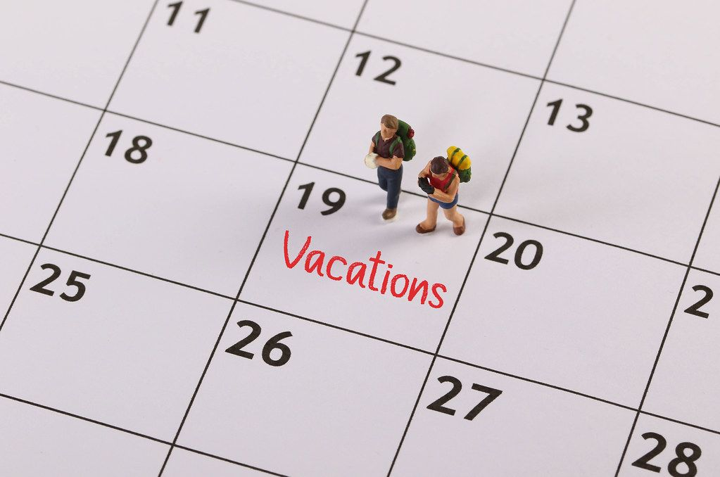 Small traveler figures with backpack standing on calendar with Vacations text