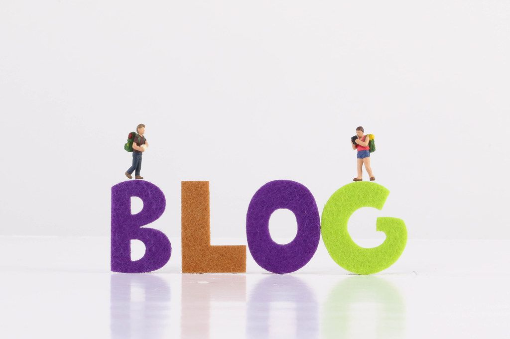 Small traveler figures with Blog text on white background