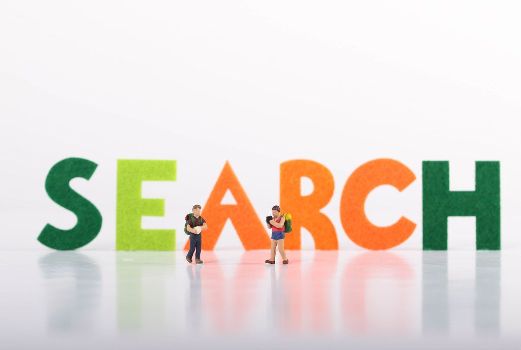 Small traveler figures with Search text on white background