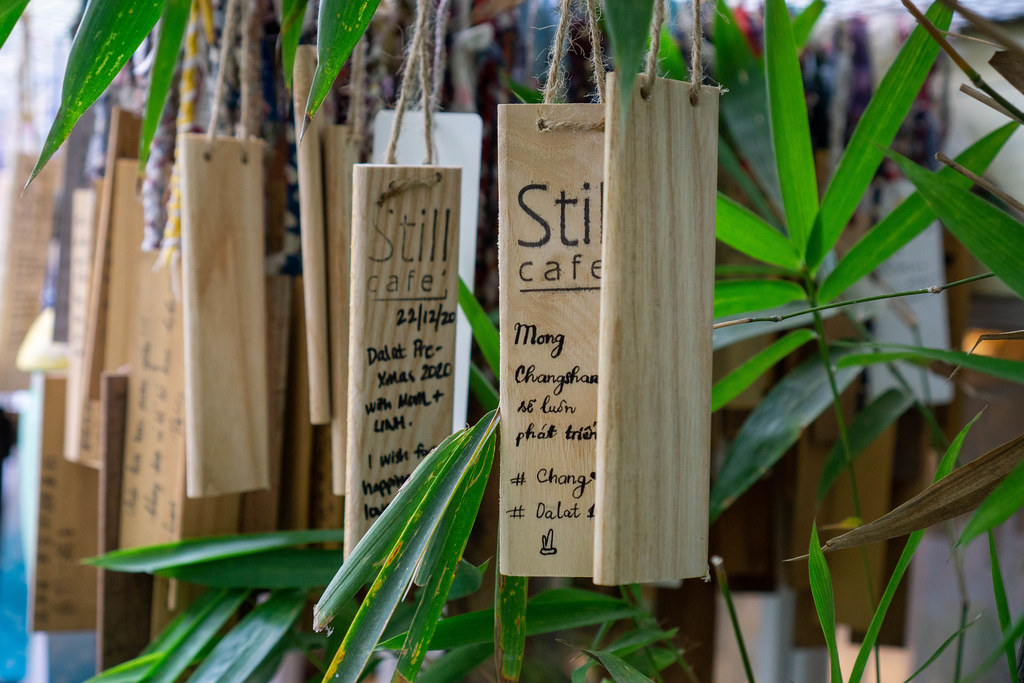 Small Wooden Boards with Wishes and Greetings from Guests hanging in the Garden of Still Cafe in Da Lat, Vietnam