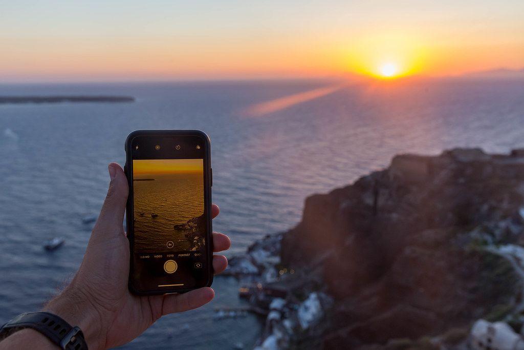 Smartphone-Fotografie in Urlaub: Mann mit iPhone in der Hand fotografiert den Sonnenuntergang