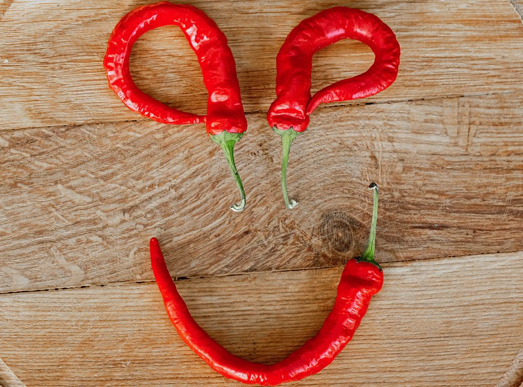 Smiley made of chili peppers on wooden background, top view