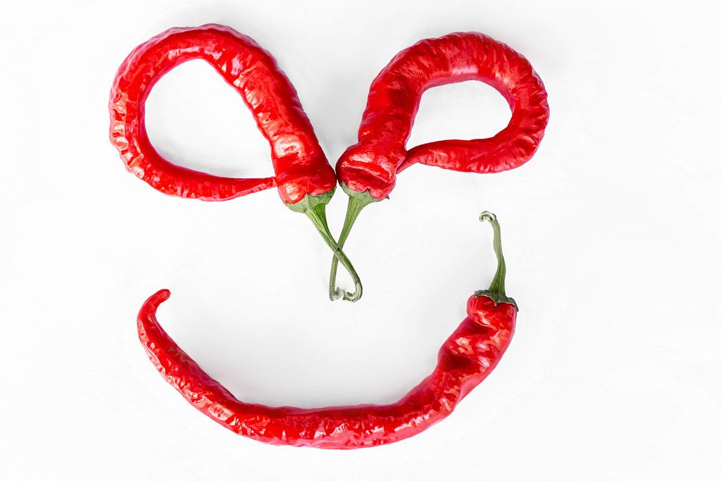 Smiling face made from chili peppers on white