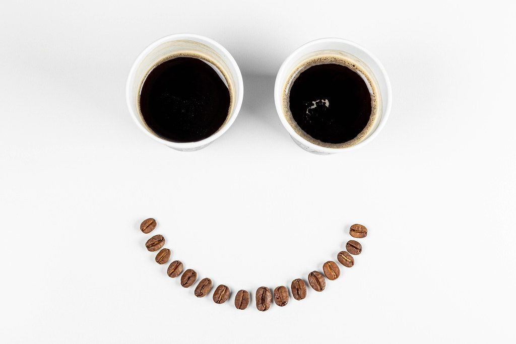 Smiling face - with coffee beans mouth and eyes from two paper cups of coffee. The concept of a good mood, a good start to the day