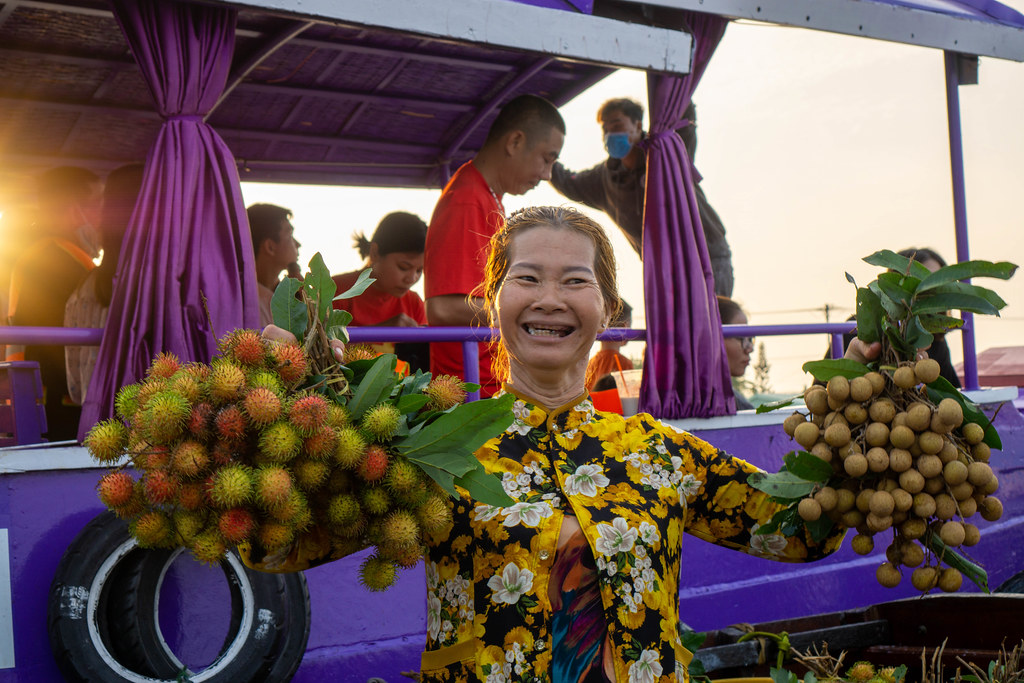 Smiling Woman selling Exotic Fruits Rambutan and Longan at Cai Rang Floating Market from a Boat in Can Tho, Vietnam
