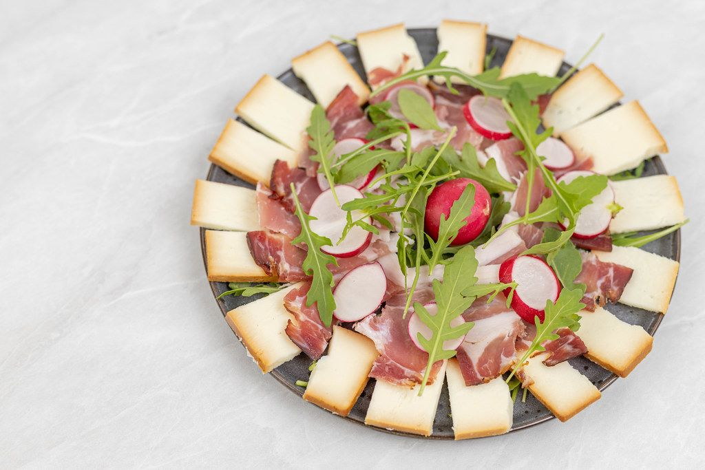 Smoked cheese with swiss ham and Rucola served on the plate