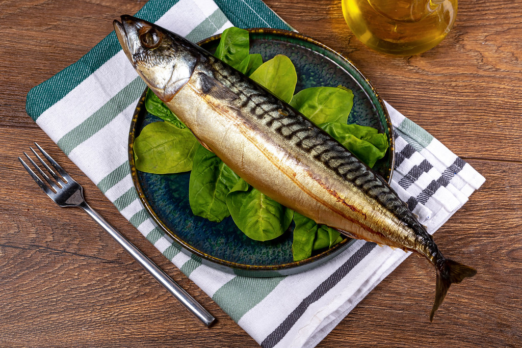 Smoked mackerel with spinach leaves in a plate on a wooden background