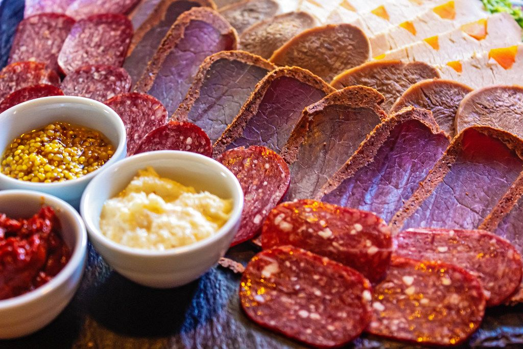 Smoked salami, dried meat and baked fillets with different sauces