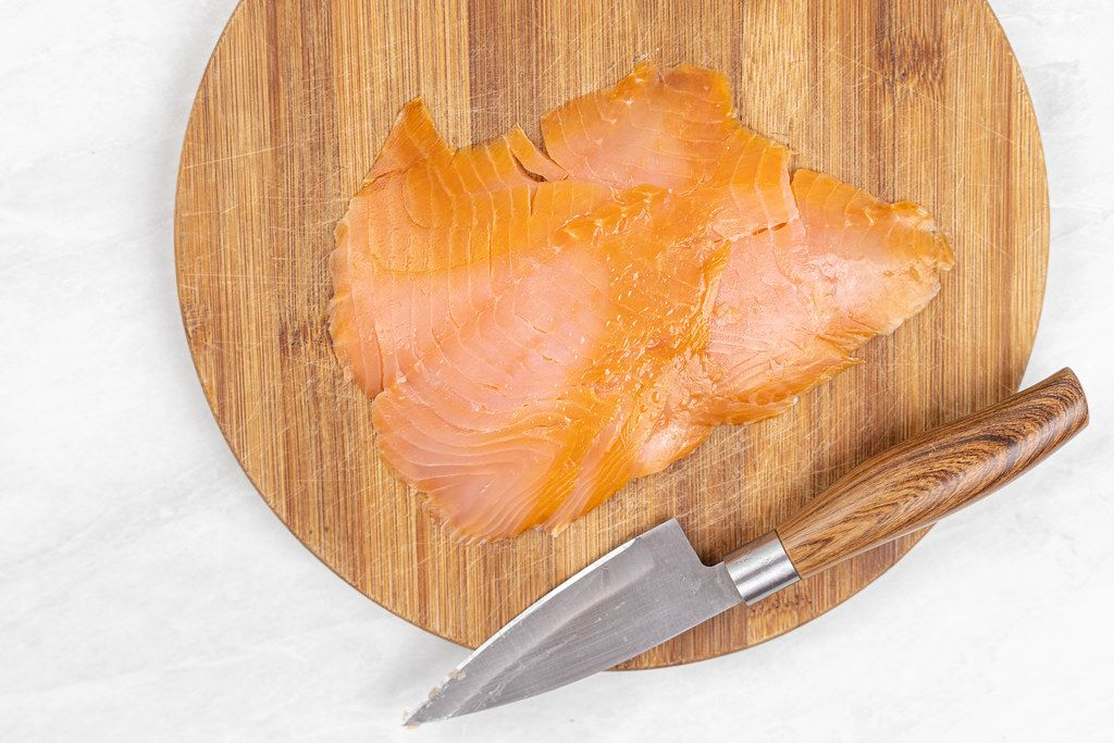 Smoked Salmon filet on the wooden cutting board with knife