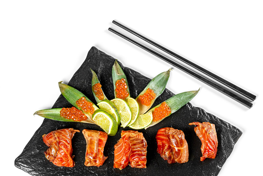 Smoked salmon fillet with lime and red caviar on green leaves