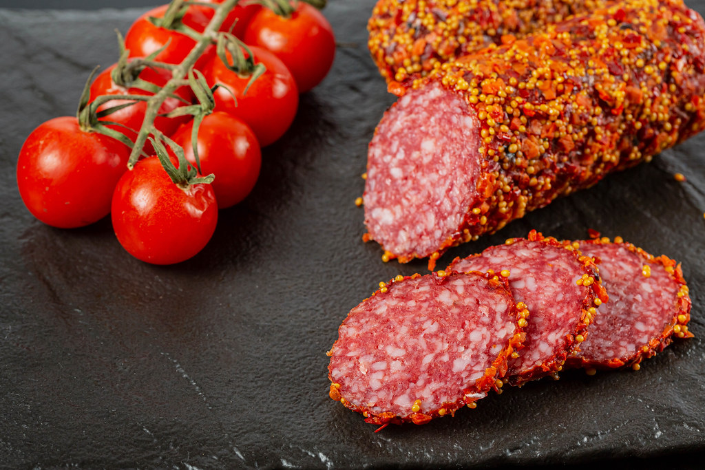 Smoked sausage with mustard seeds, paprika and tomatoes on a dark background