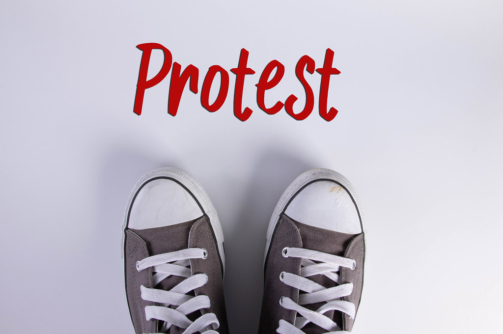 Sneakers and Protest text on white background