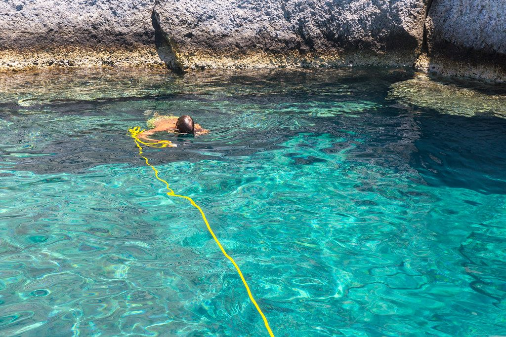 Snorkeling in turquoise waters during a stop of a boat excursion along the coast of Milos, Greece