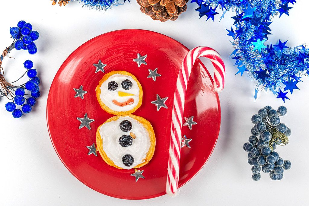 Snowman made of pancakes with striped lollipop stick and stars