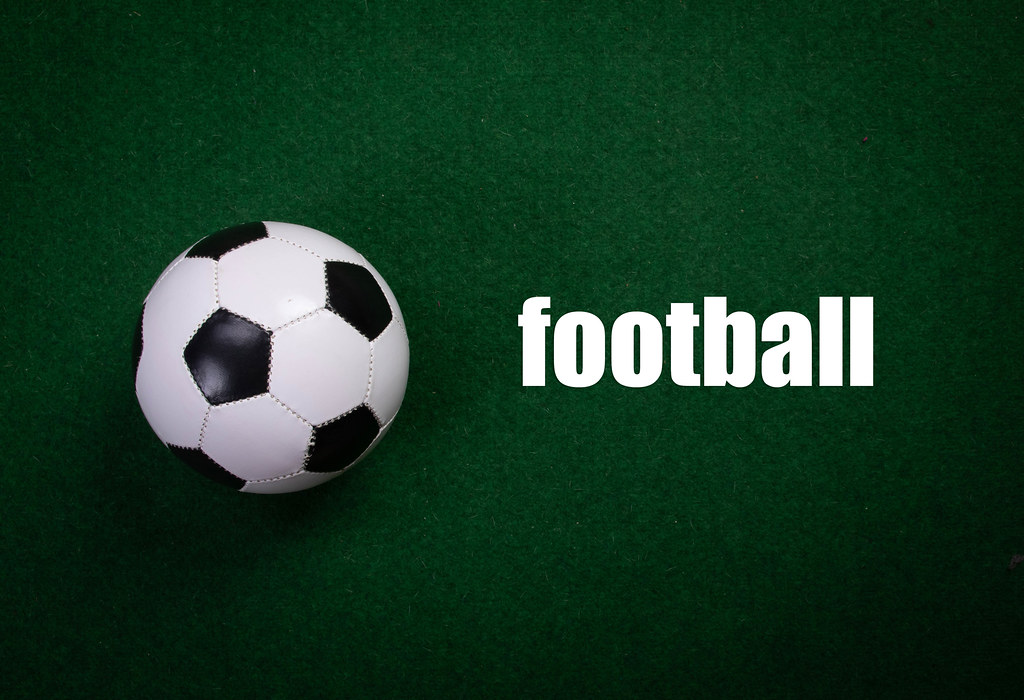 Soccer ball and football text on green grass