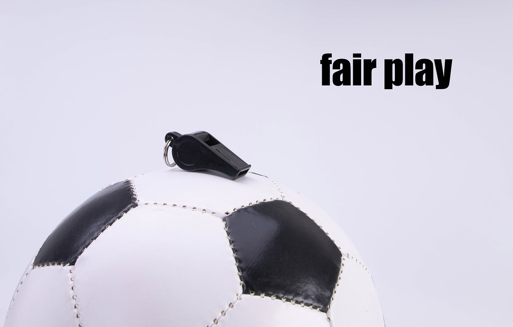 Soccer ball and sports whistle with Fair play text on white background