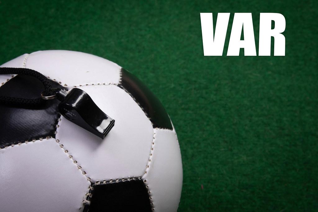 Soccer ball and VAR text on green grass
