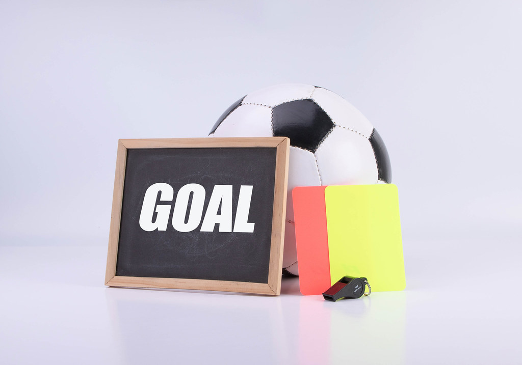 Soccer ball, referee cards and chalkboard with Goal text