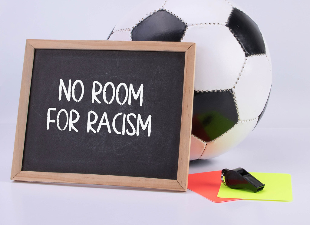 Soccer ball, referee cards and chalkboard with No room for racism text