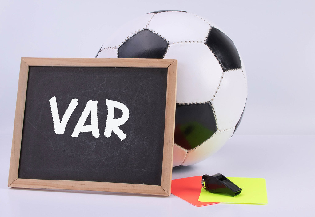 Soccer ball, referee cards and chalkboard with VAR text