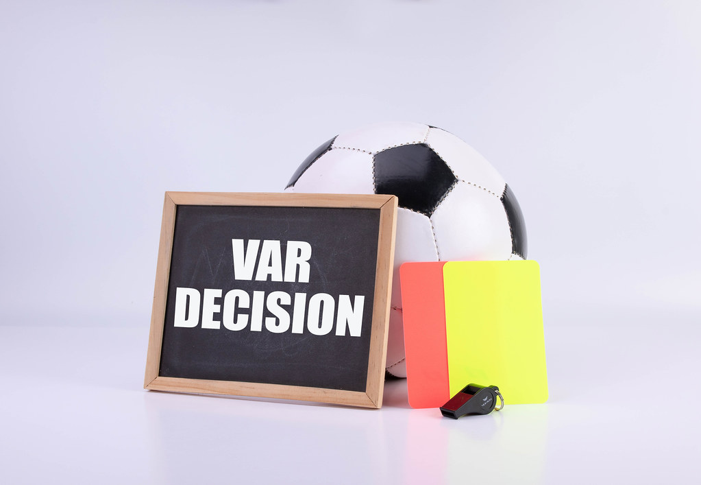 Soccer ball, referee cards and chalkboard witt VAR decision text