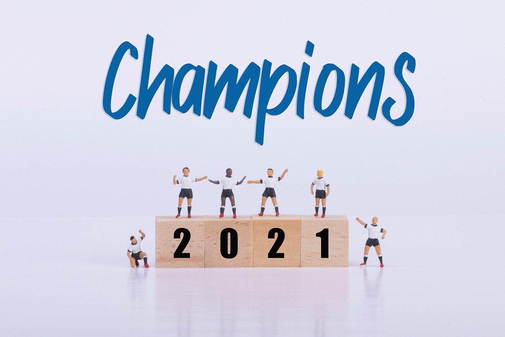 Soccer players standing on wooden cubes with 2021 text and Champions text