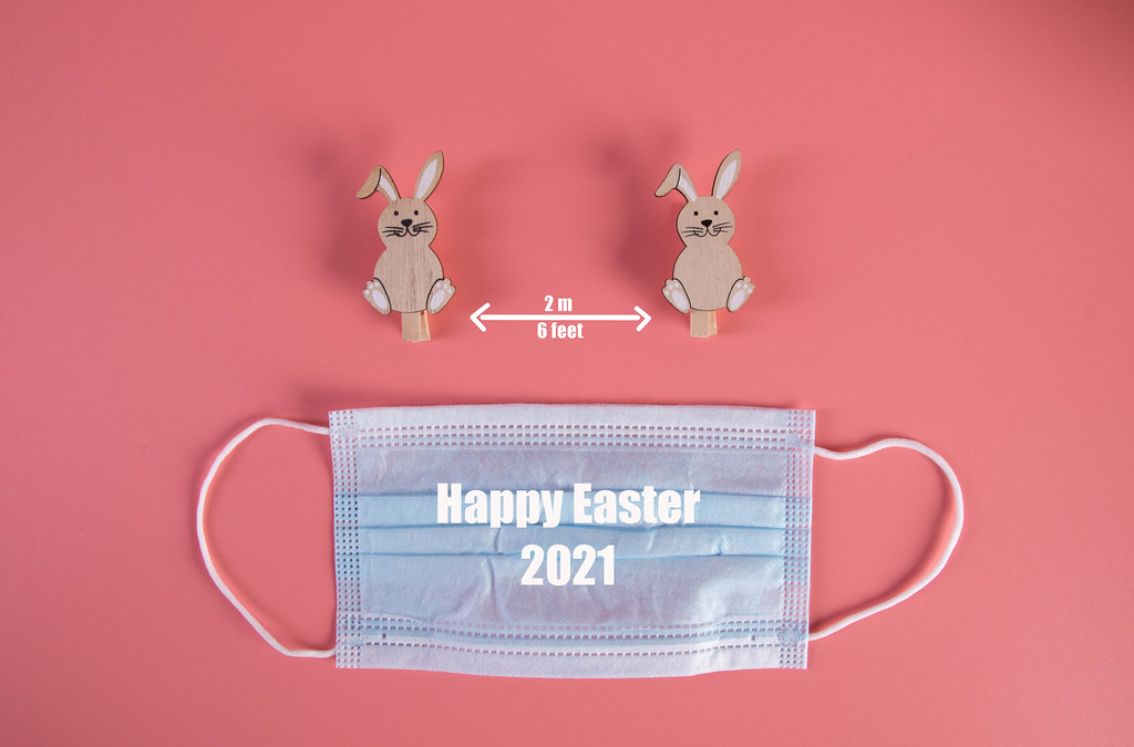 Social distancing concept with cute Easter bunnies, medical face mask and Happy Easter 2021 text