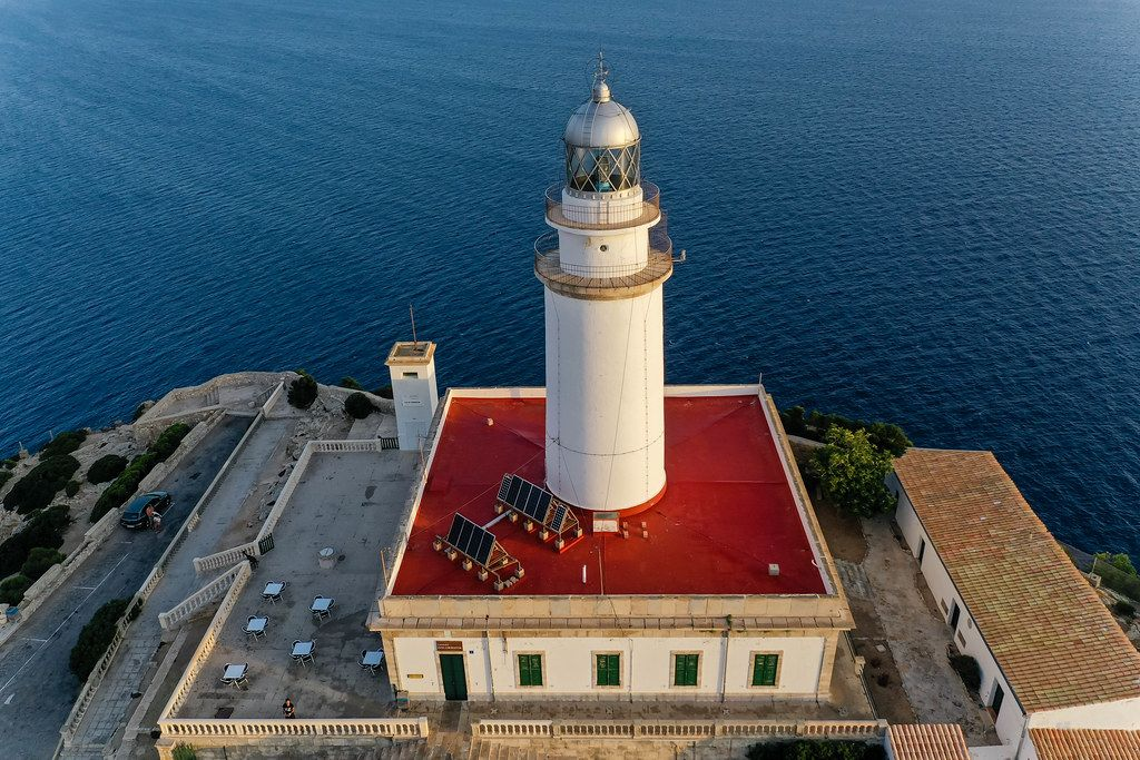 Solar panels on the red roof of the lighthouse at Cap de Formentor, Mallorca, seen against the blue sea