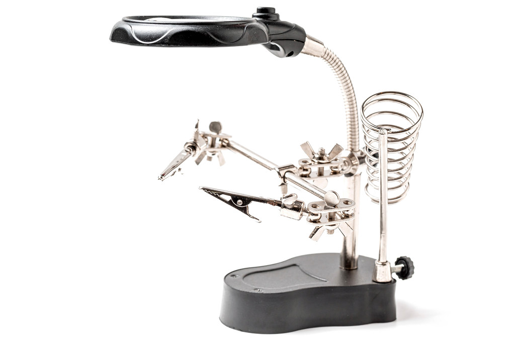 Soldering stand with helping clamps and magnifying glass on white background