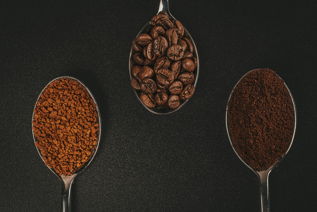 Soluble coffee, coffee beans and ground coffee isolated on black background, top view