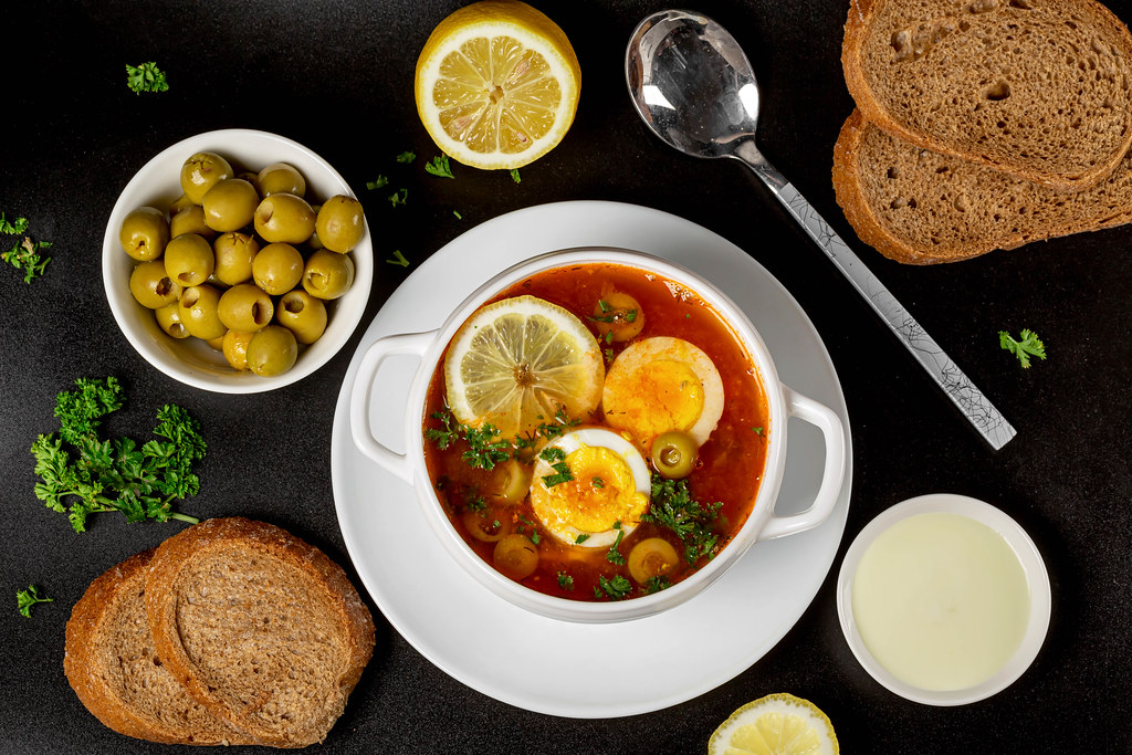 Solyanka soup on a dark background with olives, lemon, bread and herbs, top view