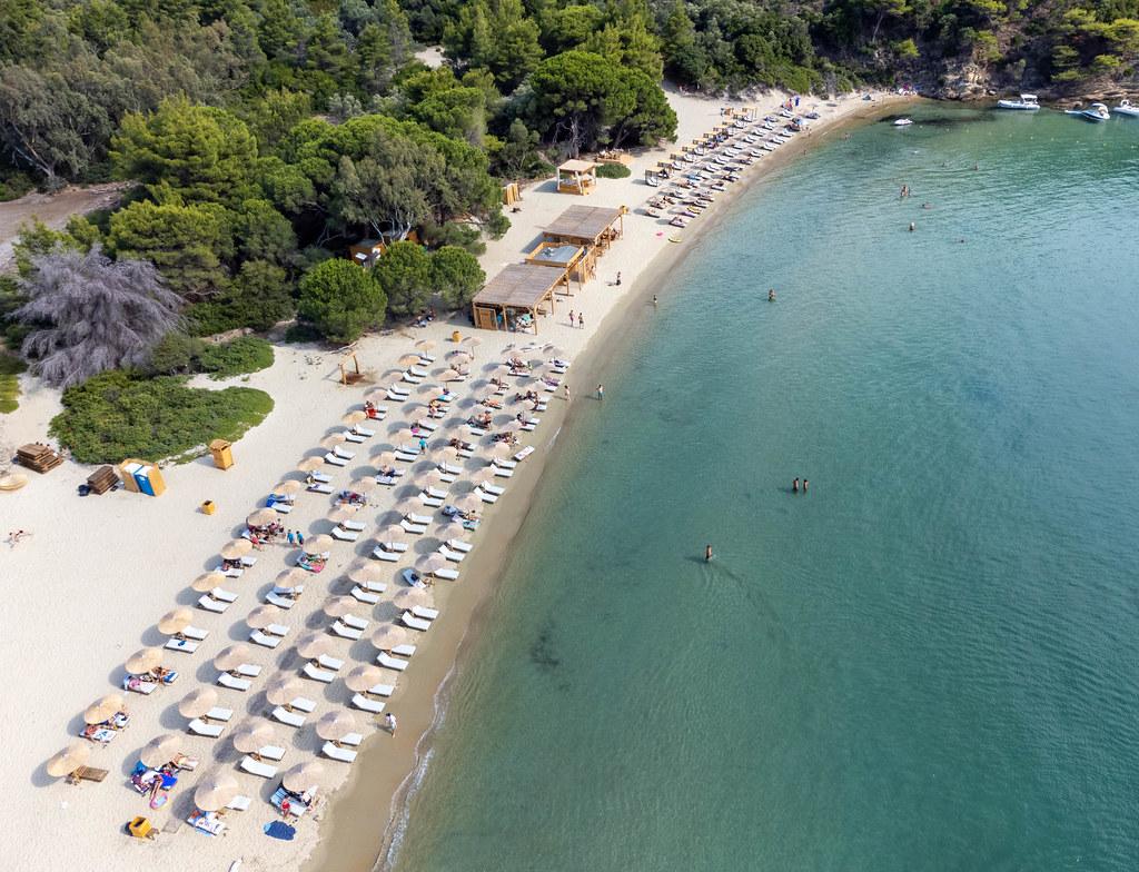Sommer in Griechenland: vier Reihen Sonnenschirme mit Sonnenliegen am Tsougria Strand