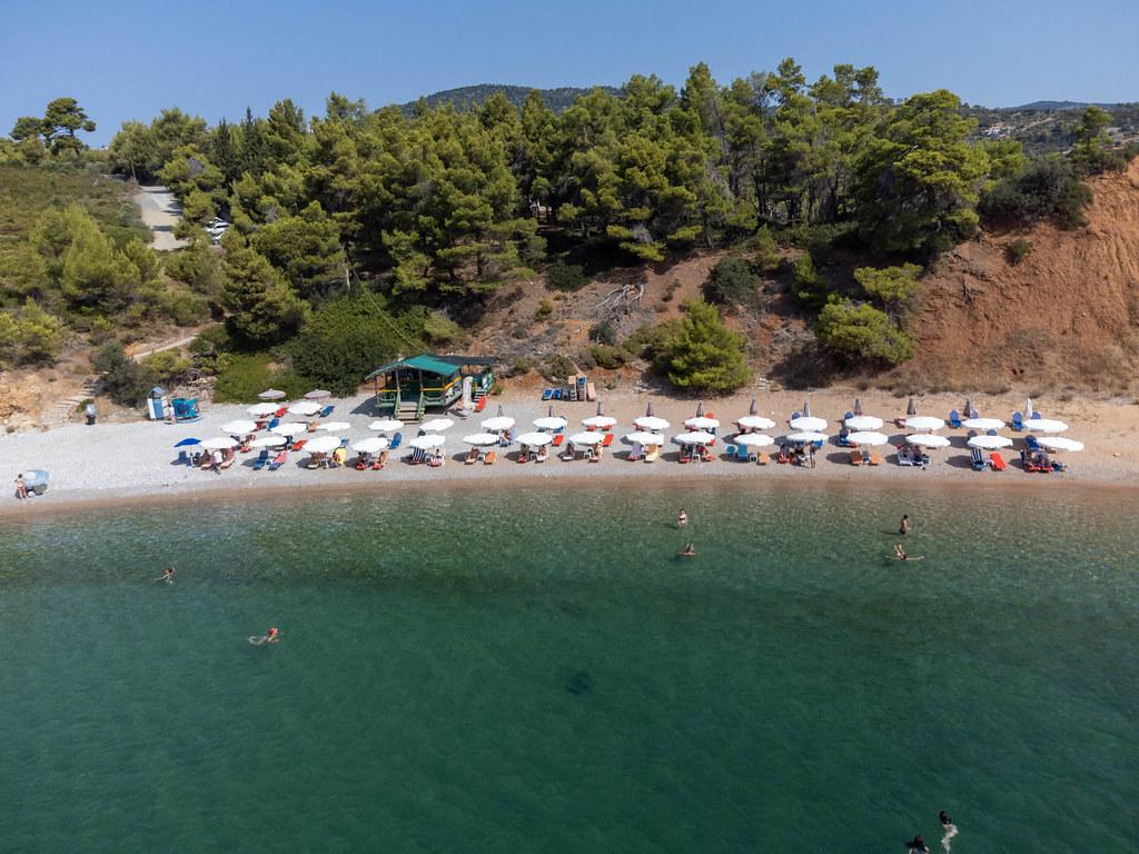 Sommerurlaub 2021 auf Alonnisos, Griechenland. Der Strand von Kokkinokastro mit weißen Sonnenschirmen