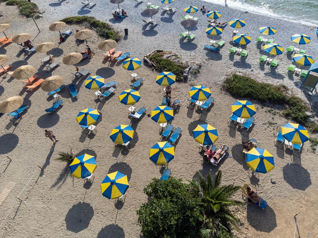 Sommerurlaub 2021 in Griechenland mit Abstand zwischen den blau-gelben Sonnenschirmen am Strand Milia
