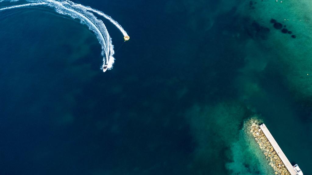 Sommerurlaub 2021 in Griechenland. Motorboot schleppt Aquadonut. Aufnahme von oben