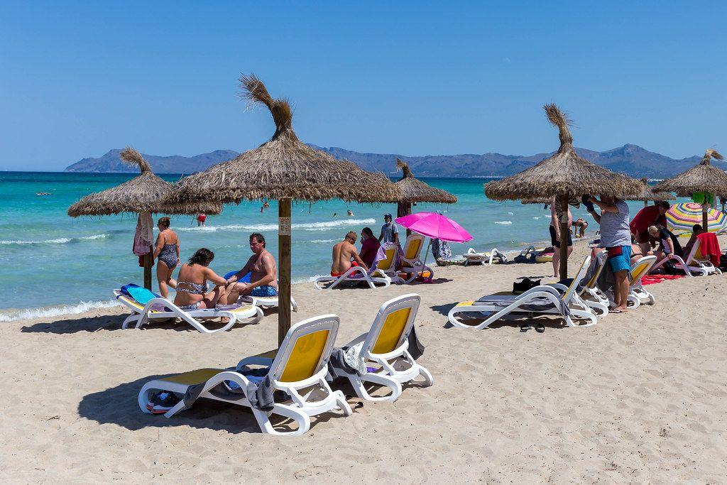 Sonnenschirme aus Stroh und Sonnenliegen. Touristen am Strand auf Mallorca im Sommer 2020