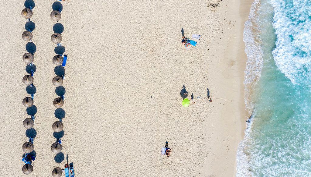 Sonnenschirme aus Stroh und Touristen. Overhead-Luftbild von Cala Mesquida Strand, Mallorca