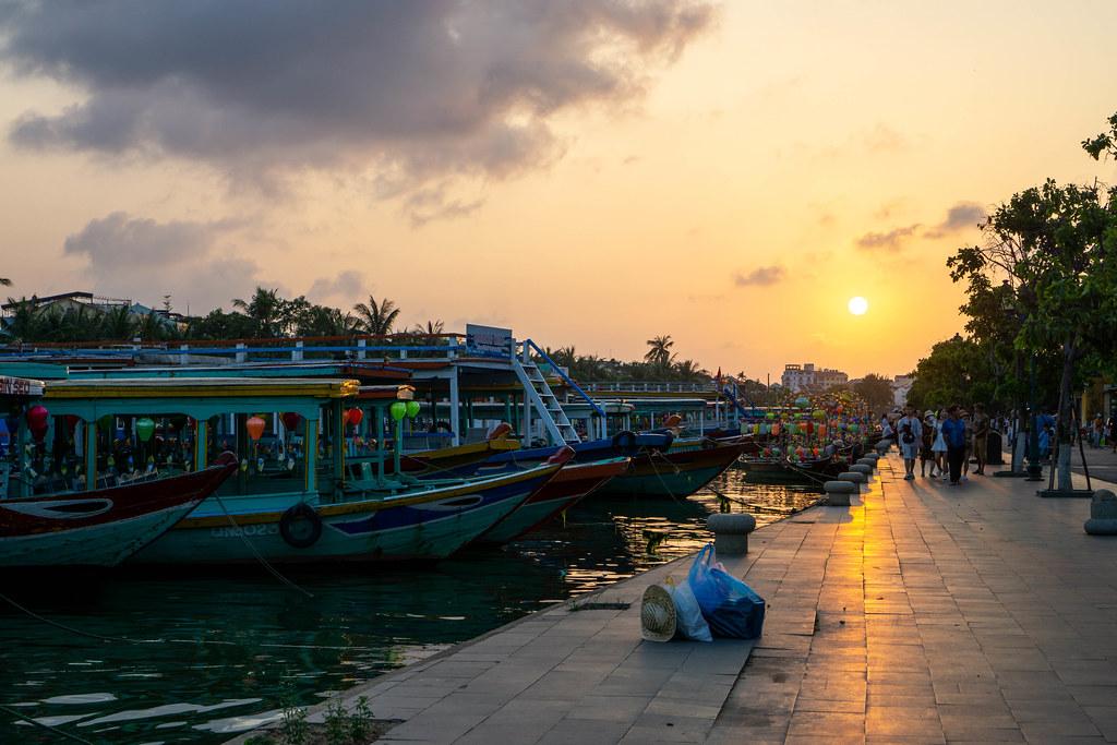 Sonnenuntergang am Flussufer des Thu Bon Fluss mit vielen angelegten Touristenbooten in der Altstadt von Hoi An, Vietnam