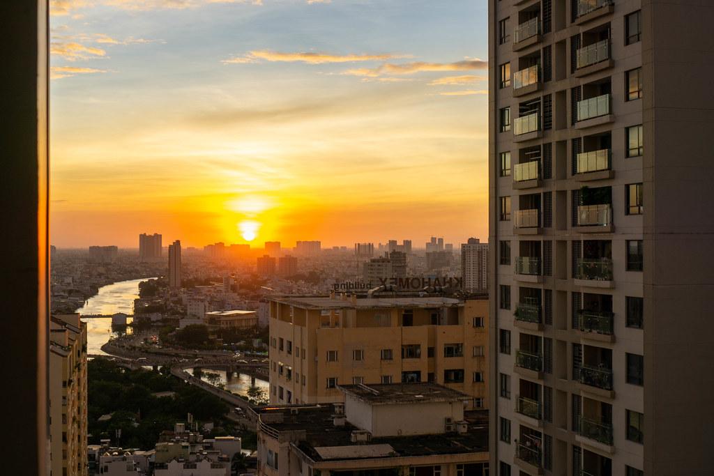 Sonnenuntergang zur Goldenen Stunde mit Ausblick auf Saigon River, Apartment Gebäude und Stau auf der Nguyen Van Cu Brücke in Ho Chi Minh Stadt, Vietnam