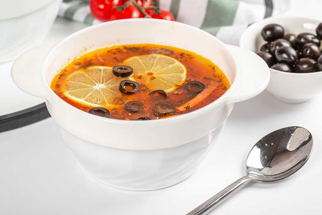 Soup solyanka with meat, sausages, vegetables, pickles, olives and lemon
