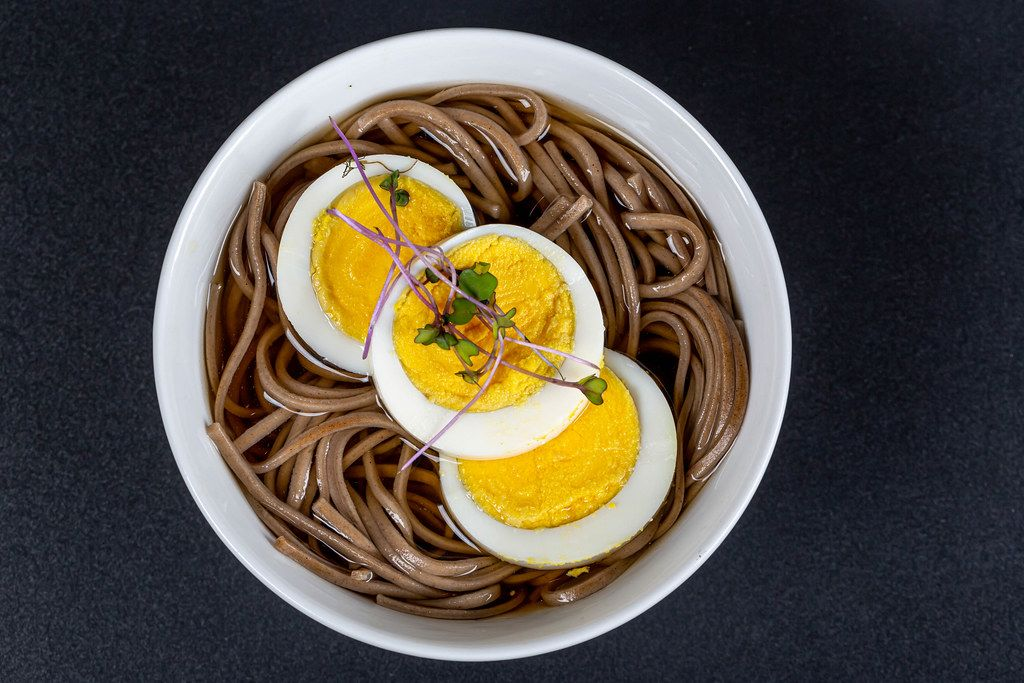 Soup with buckwheat noodles, boiled egg and micro-greens of cabbage, top view