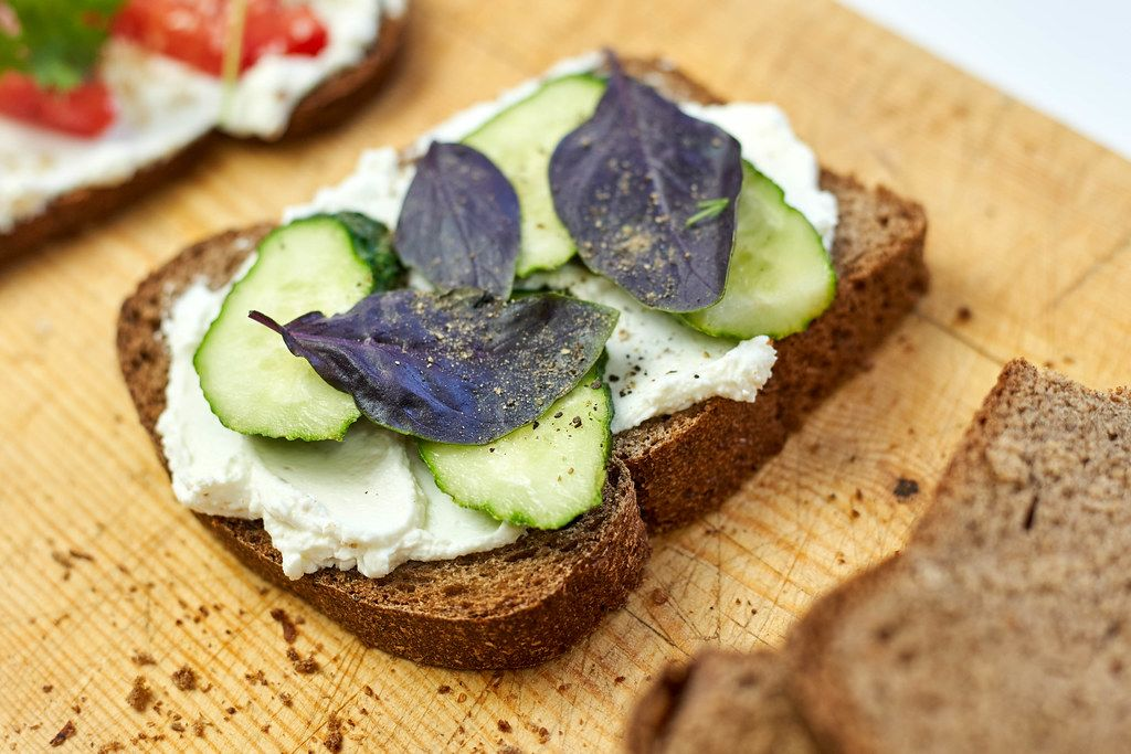 Sour cream spread on toast with cucumber slices and basil leaves