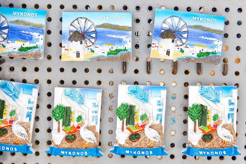 Souvenirs of Mykonos, magnets with windmills and view of the port, alley with goose, plants and fruit