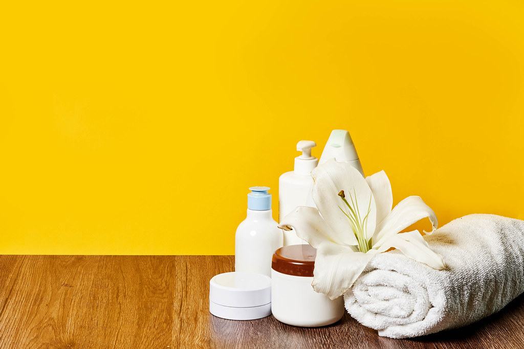 Spa beauty background with tools and cosmetics: creams, oils and towels on against yellow background