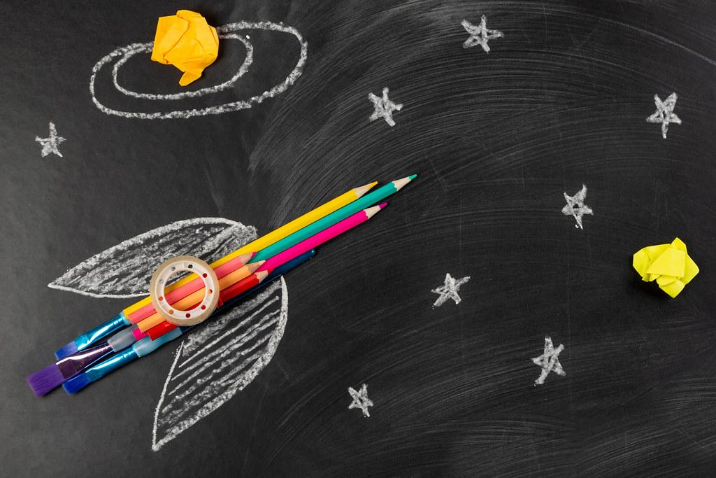 Spaceship or rocket made of school supplies on a dark background with chalk drawn stars
