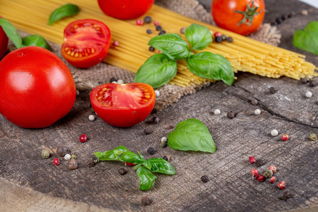 Spaghetti and tomatoes with herbs on an old wooden background