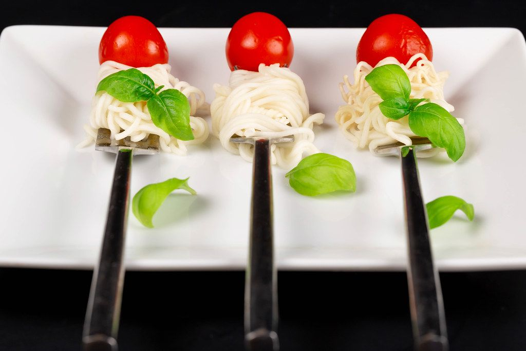 Spaghetti with basil and cherry tomatoes on forks