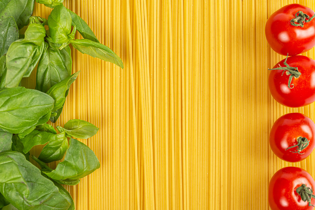 Spaghetti with basil leaves and cherry tomatoes, top view