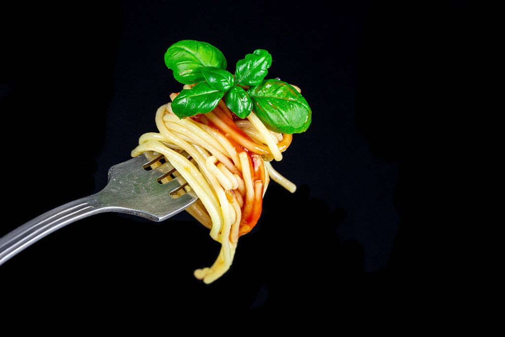Spaghetti with tomato sauce and basil leaves on a fork, close-up